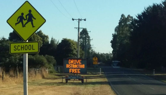 Image of mobile message board on roadside displaying road safety message