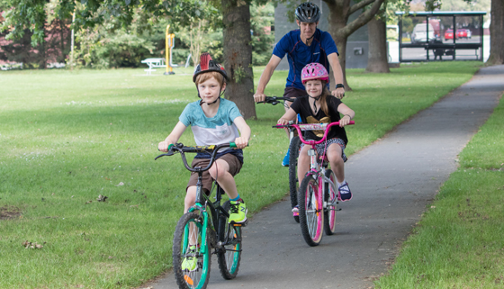 Family riding bikes on a sealed pathway through a park