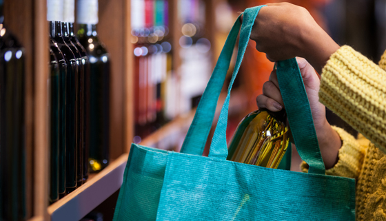 Woman putting alcohol in bag