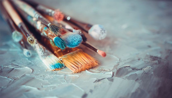 Colourful image of paint brushes resting on a desk
