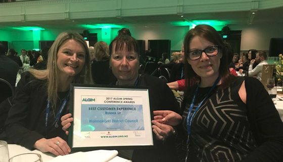 Three WDC customer service staff holding certificate