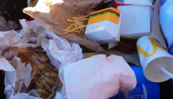 Recycling bin showing food and non-recyclable items