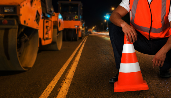 Road workers working on an asphalt surface at night